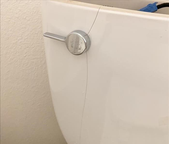 toilet tank with a leaking crack